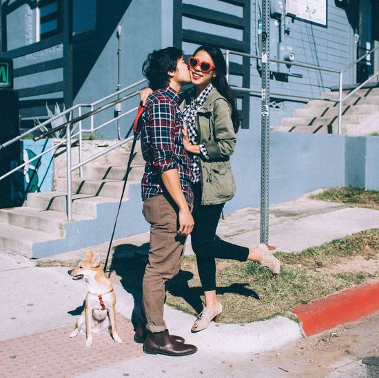 Loving Boyfriend Kissing Girlfriend While Standing By Dog During Sunny Day