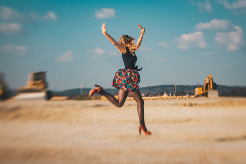 Full length of woman jumping against sky