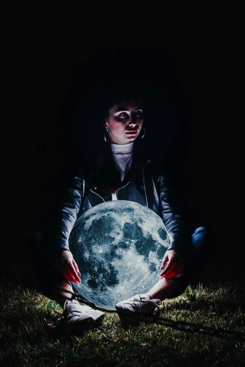 Young woman holding illuminated sphere while sitting on land at night
