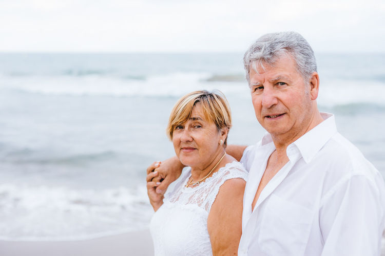 Sea Two People Togetherness Beach Portrait Water Couple - Relationship Men Males  Heterosexual Couple Adult Senior Adult Land Emotion Looking At Camera Women Love Females Smiling Mature Adult Positive Emotion Mature Men Horizon Over Water Mature Couple Wife