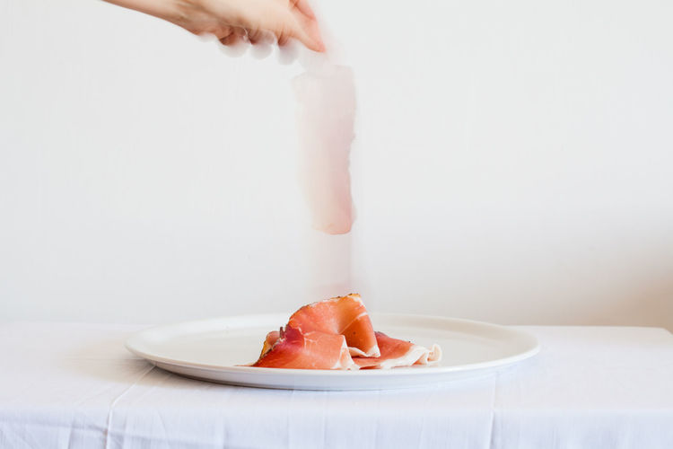 hand plate up ham, white set. long exposure Close-up Dish Fallen Falling Food Food And Drink Ham Healthy Eating Human Hand Indoors  Long Exposure Plate Plate Uo Prosciutto SLICE Speck Studio Shot Food Stories