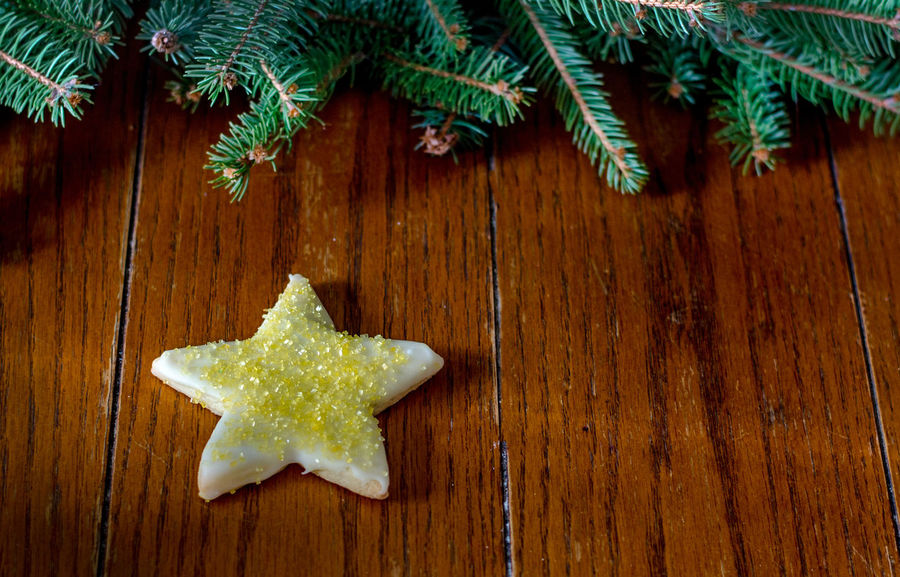 a sweet yellow star sugar cookie on a wood background with garland and room for text Christmas Christmas Cookies Sweet Treat Treat Yourself Christmas Close-up Day Food Food And Drink Freshness Green Color Holi Indoors  No People Star Cookie Sugar Cookies Sweets Table Wood - Material Yellow Star