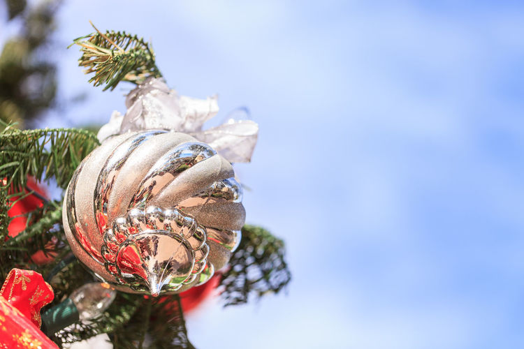 Low angle view of bauble hanging on christmas tree against sky