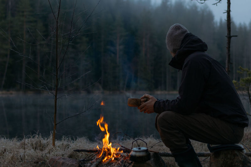 Side view of mid adult man camping in forest during winter at dusk