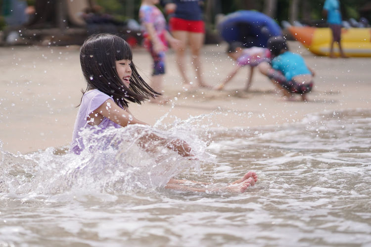 Child Childhood Day Emotion Enjoyment Females Fun Girls Innocence Leisure Activity Lifestyles Motion Outdoors People Positive Emotion Real People Splashing Two People Water Waterfront Women
