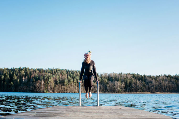 Full length of man in swimming pool against clear sky