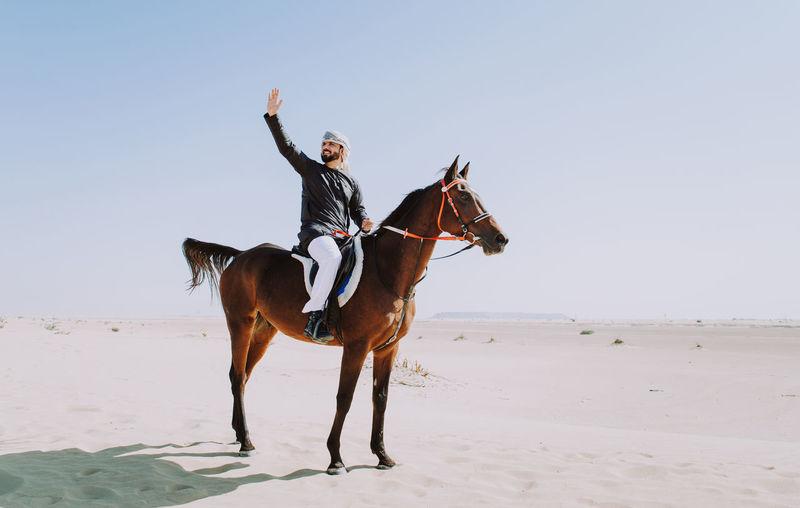 Man waving while sitting on horse in desert against sky
