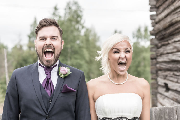 Portrait Of Smiling Bride And Groom With Mouth Open In Yard