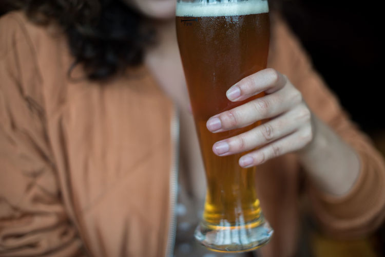 Close-up of woman holding beer glass