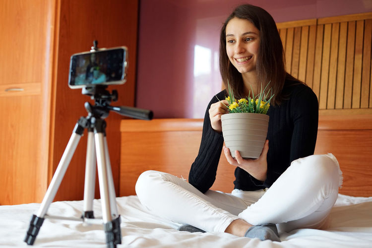 Portrait of smiling woman holding camera at home
