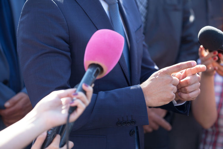 Media interview. Hand gesture. News conference. Journalist PR Reporting Broadcasting Broadcasting Journalism Business Person Gesture Hand Gesture Human Hand Journalism Media Event Media Interview Microphone News News Conference People Politician Public Relations Publicity Question Spokesman Spokesperson Unrecognizable Person