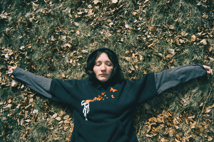 A girl with closed eyes and arms crossed resting on the ground in nature