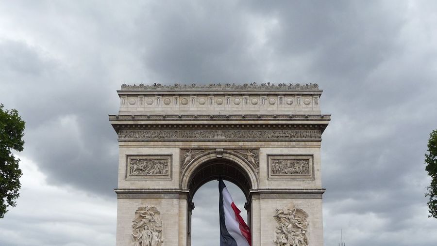 High section of triumphal arch against cloudy sky