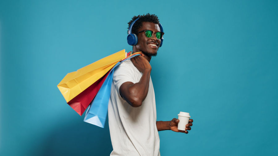 Portrait of young man wearing sunglasses standing against blue background
