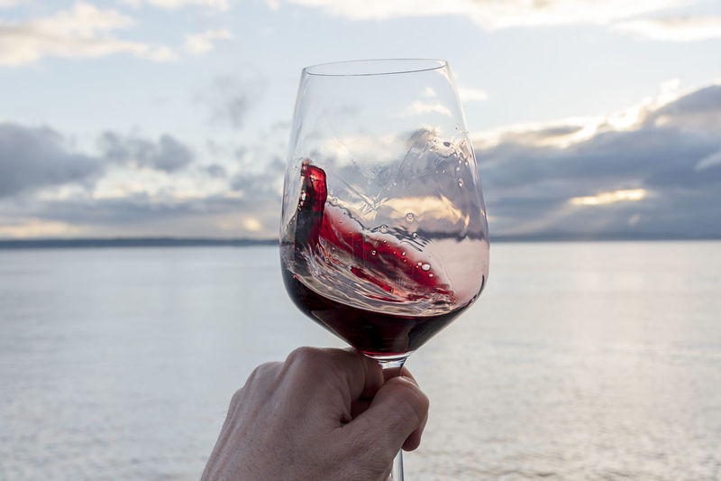 Swirling red wine point of view over sea with dramatic sunset sky.