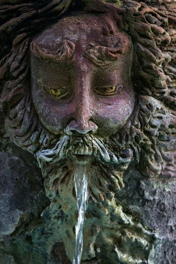 Close-Up Of Water Flowing From Human Sculpture