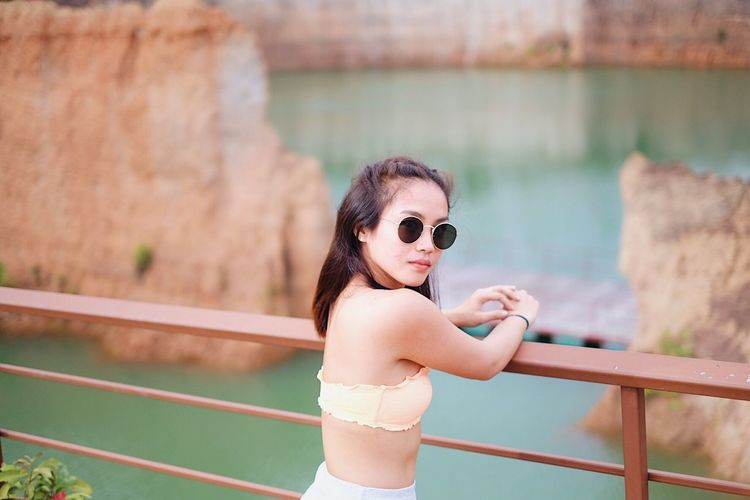 Portrait of young woman in sunglasses against railing