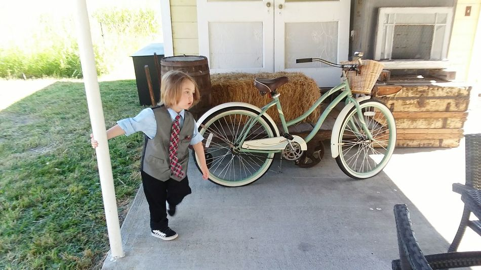 Waiting for the wedding to start at the Yellow Barn Full Length Child Childhood Standing Window Building Exterior Architecture Stationary Bicycle Handlebar Wheel Bicycle Basket Tire Spoke