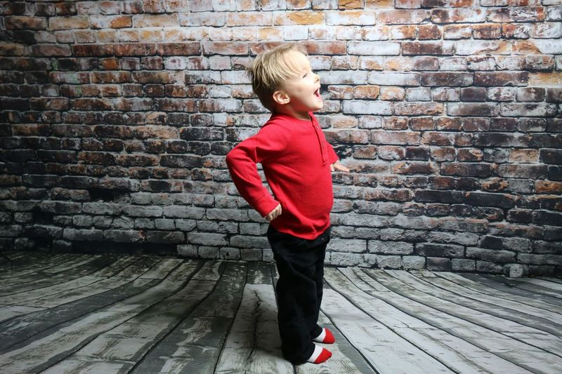 Full Length Of Boy Standing Against Brick Wall