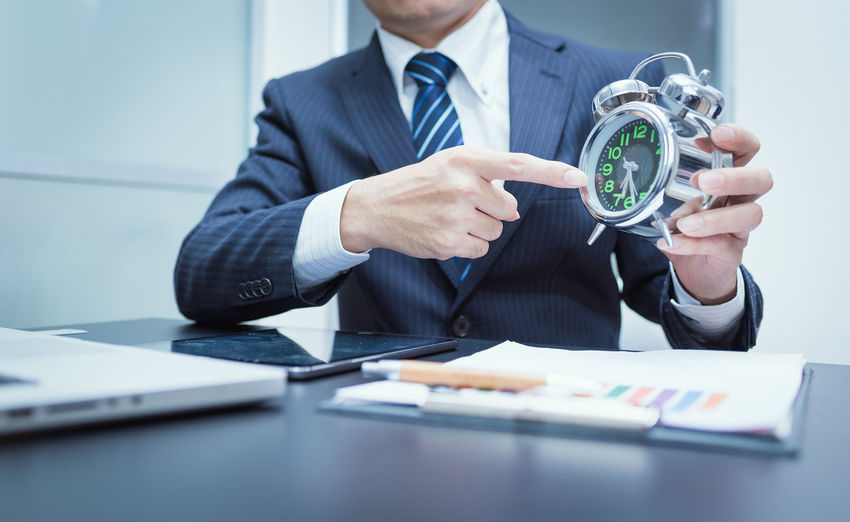 Midsection of businessman holding alarm clock at desk in office