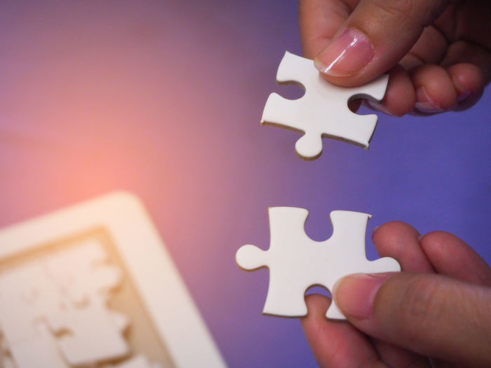 Cropped hands holding jigsaw pieces over table