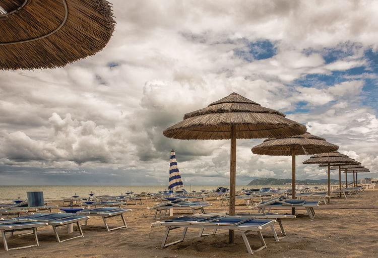 Lounge chairs and parasols at beach against cloudy sky
