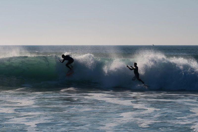 Men surfing in sea against clear sky