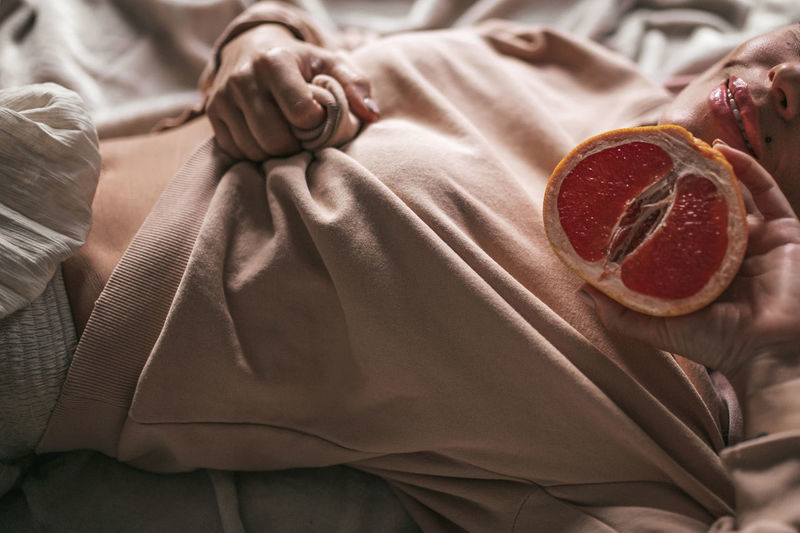 Midsection of woman with grapefruit lying on bed at home