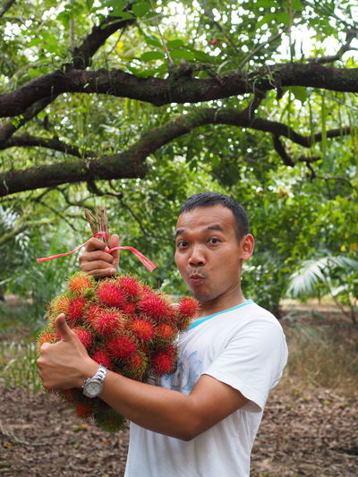 Portrait of man holding lychees while standing in forest