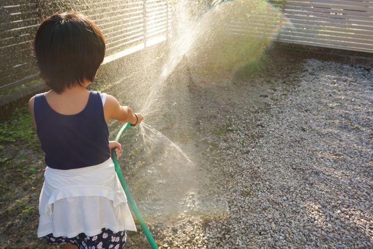 Rear view of girl spraying water at back yard