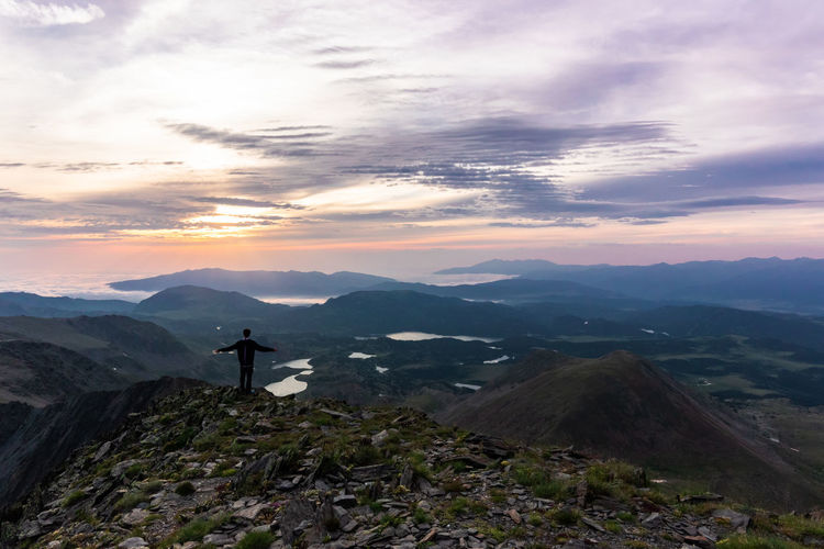Standing at the top of Pic Carlit during sunrise Mountain Tranquil Scene Real People Environment Lifestyles Looking At View Outdoors Standing Mountain Range Beauty In Nature One Person Nature Idyllic Rewilding Sunrise Lakes  Morning Top Of The Mountains