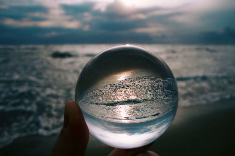 Close-up of hand holding crystal ball against sea
