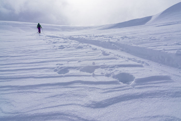Rear View Of Person Skiing On Snow Covered Landscape