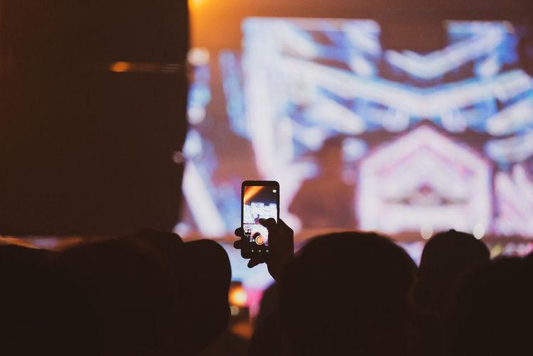 People photographing illuminated smart phone at night