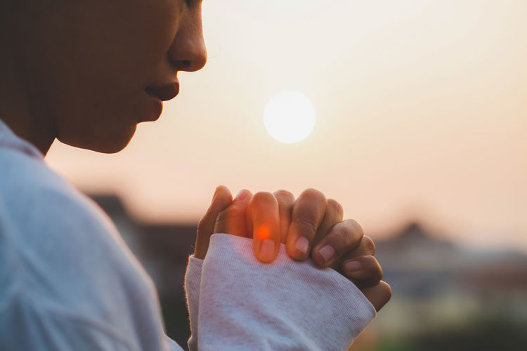 Midsection of woman with hands clasped outdoors during sunset