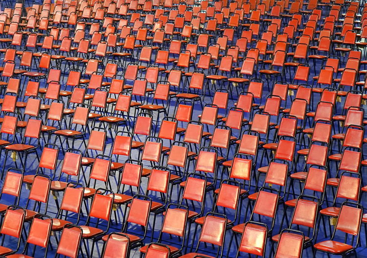 Rows of red chairs and seats at a public event Event Meeting Perspective Red Auditorium Chair Conference Empty Large Group Of Objects Metal Frame No People Pattern Plastic Seat Stools Upholstered