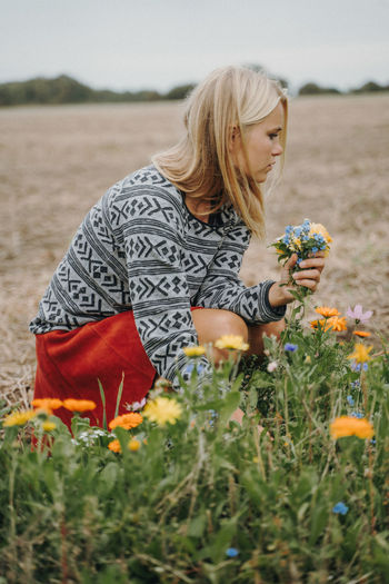 Woman Picking Flowers On Field