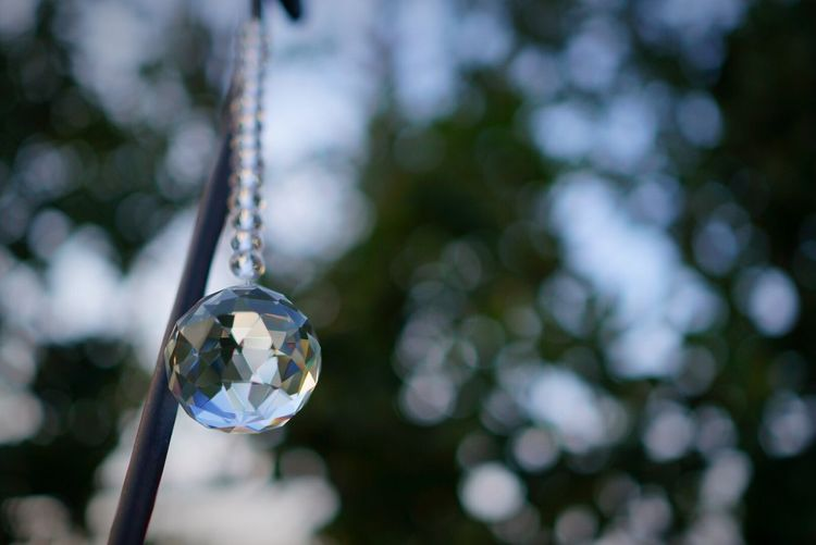 Crystal ball hanging from stick in yard
