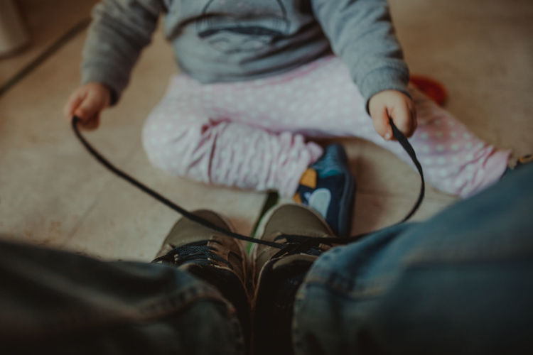 Low section of baby tying man shoelace on floor