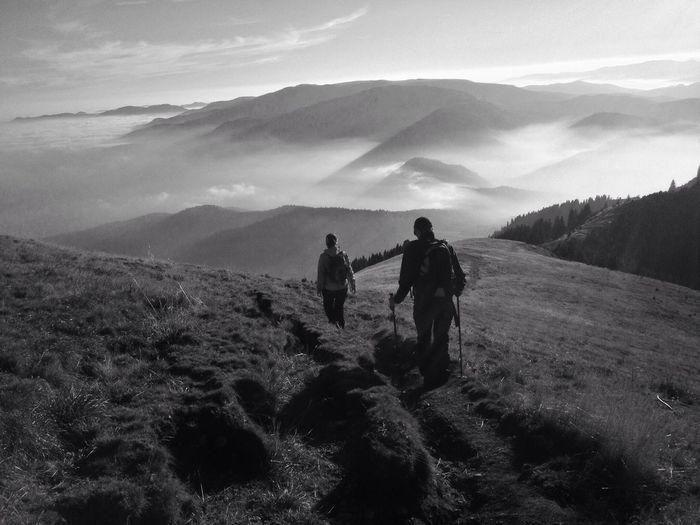 Rear view of two people walking on landscape