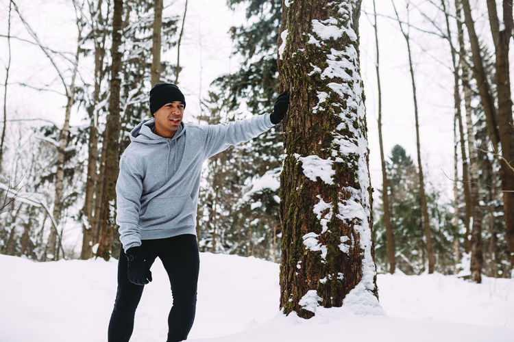 Low Angle View Of Tired Man Standing In Forest During Winter