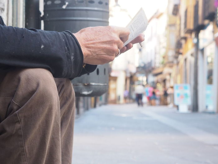 Midsection Of Man Holding Newspaper By Street