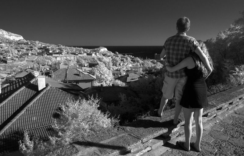 Rear View Of Couple Looking At Townscape By Sea