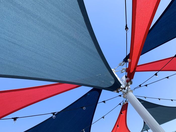 Low angle view of red and blue sun sail against clear sky