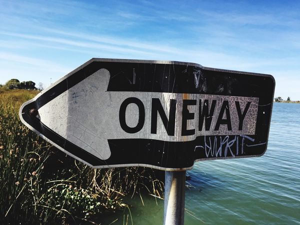 One way Vandalised Directional Sign Riverside Street Sign Damaged Entropy Defaced Text Western Script Communication Guidance Day Capital Letter Sky Road Sign Outdoors No People Sunlight Nature Close-up
