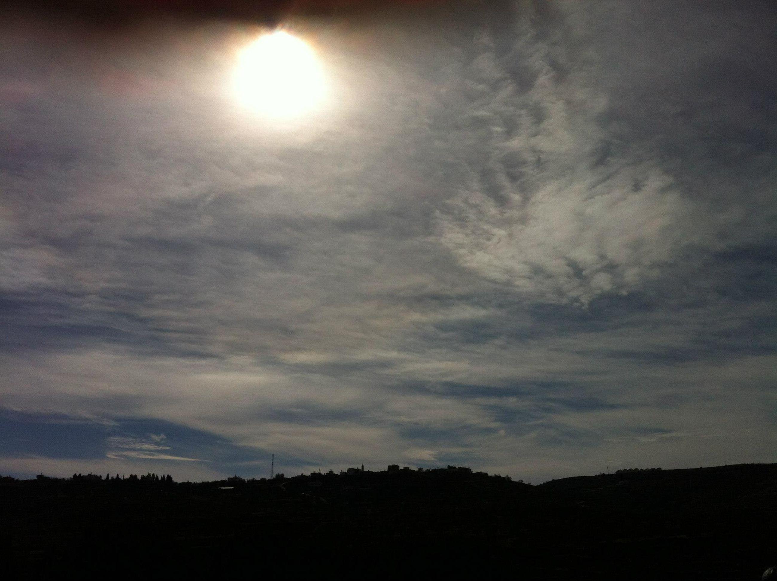 silhouette, sky, tranquil scene, tranquility, scenics, sun, beauty in nature, sunset, cloud - sky, landscape, nature, cloudy, sunbeam, idyllic, cloud, sunlight, dark, low angle view, outdoors, dusk