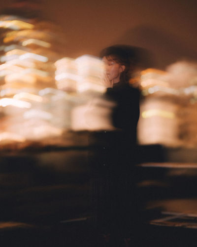 Blurred motion of man standing on wall at night