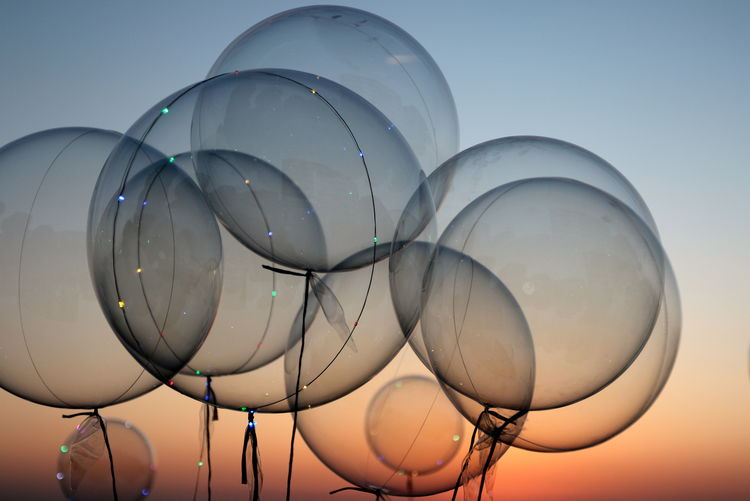 Close-Up Of Helium Balloons Against Sky At Dusk Balloon Balloons Circles Clear Sky Close-up Day Dusk Fragility Helium Balloon Inflatable  No People Outdoors Repetition Simplicity Sky Sunset Transparent Plastic Environment - LIMEX IMAGINE