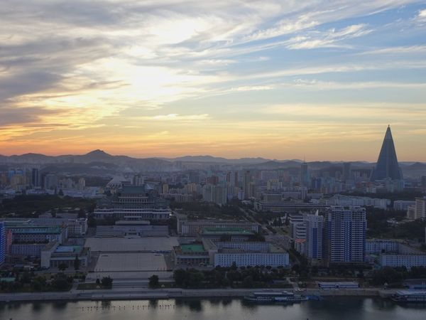 City Skyline DPRK DPRKorea Korea North Korea Orange Sky Pyongyang Streets Ryugyong Scenic View Clouds Empty Ghost Town Hotel Mountains Pyongyang River Scenic View Sky Still Still Life Sunset Unique Unique Country Unique Design