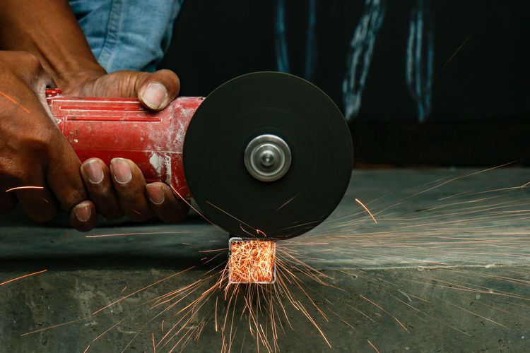 Man cutting metal in factory